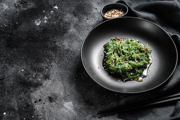 Una sana insalata di chuka di alghe con verdure. sfondo nero