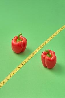 Insieme sano da due peperoni rossi della paprika e nastro di misurazione giallo diagonale come segno di percentuale su uno sfondo verde, copia dello spazio. alimento ipocalorico per la riduzione del peso.