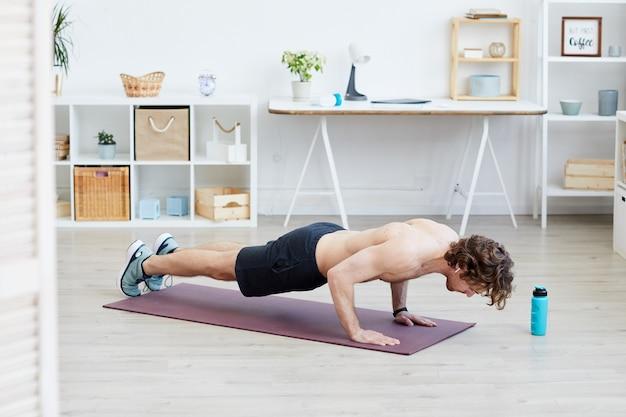 Uomo senza camicia in buona salute facendo flessioni sul tappetino per esercizi durante l'allenamento sportivo a casa