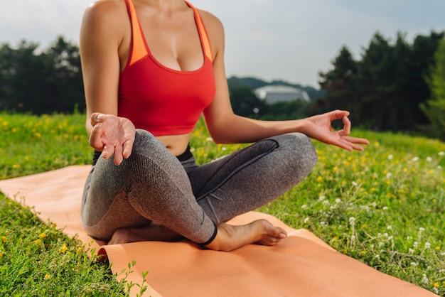 Donna sottile in buona salute che tiene insieme il pollice e il dito puntato durante il tempo di yoga
