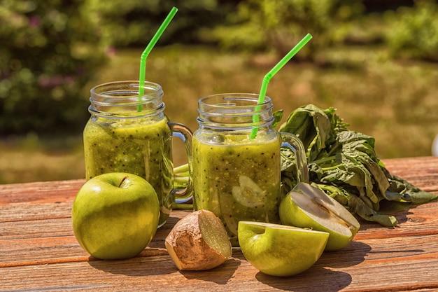 Frullato sano con spinaci, mela, sedano, kiwi, cavoletti di bruxelles, avocado, in barattoli di vetro, all'aperto, su sfondo di natura, immagine tonica.