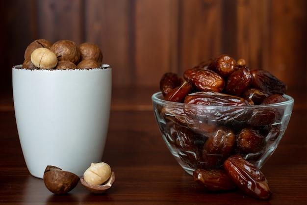 Concetto di spuntino sano. messa a fuoco selettiva. noci di macadamia e frutti di palma da datteri. primo piano di frutta secca e noci