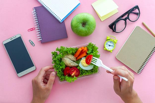 Spuntino sano dalla scatola di pranzo nel luogo di lavoro durante l'intervallo di pranzo all'ufficio. contenitore bilanciato per alimenti al lavoro. vista dall'alto