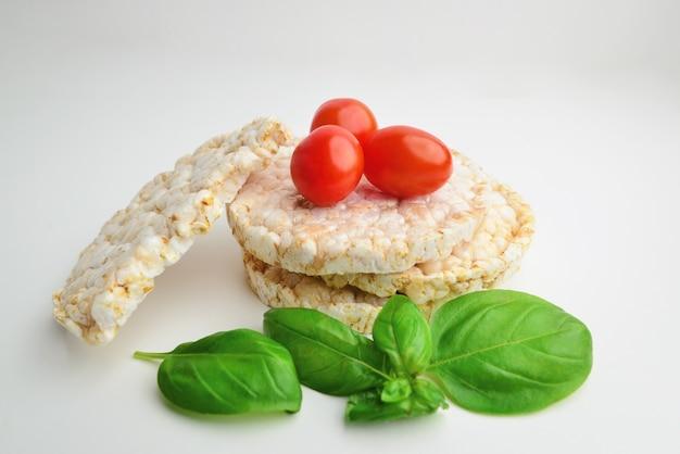 Spuntino sano dalle torte di riso. basilico e pomodori su sfondo chiaro. . spuntino di pane. cibo in fibra.