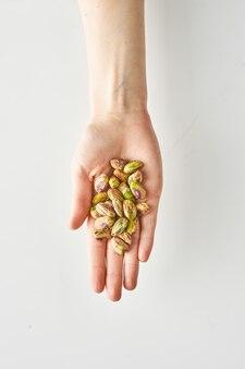 Spuntino sano di pistacchi in mano isolato