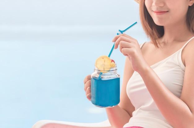 Stile di vita sano di buona salute della bevanda analcolica con la giovane donna felice che beve il succo organico degli ingredienti freschi blu delle hawaii