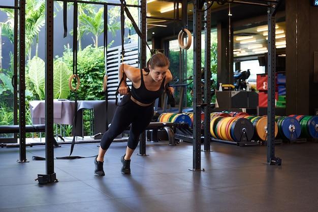Stile di vita sano e sportivo di una donna. la ragazza di forma fisica risolve facendo esercizi fisici con l'apparato di allenamento in palestra.