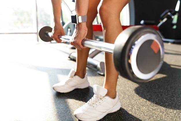 Sportiva sana facendo esercizio con bilanciere in palestra