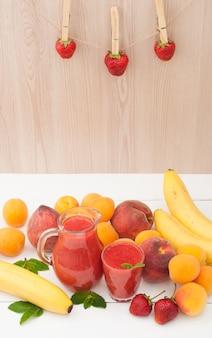 Frullato di banana sana fragola con menta in un bicchiere e brocca su fondo di legno. sfondo di banane di frutta fresca, pesche e albicocche