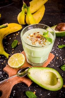 Bevanda estiva sana, frullato di avocado e banana con lime, muesli e latte di cocco, tavolo arrugginito scuro