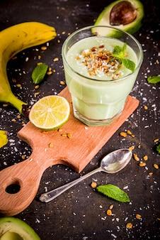 Bevanda estiva salutare, frullato di avocado e banana con lime, muesli e latte di cocco