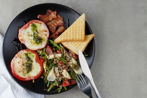 Colazione sana e gustosa. uova fritte in anelli di peperone rosso, pancetta e insalata con rucola, pomodorini, semi e formaggio a pasta dura su piastra nera