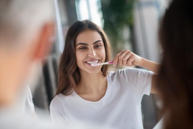 Denti sani. una donna che si lava i denti al mattino