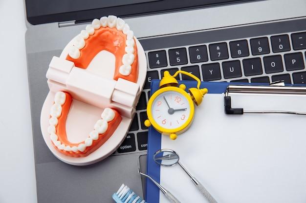 Modello di dente sano con strumento dentale e sveglia nell'ufficio del dentista. tempo per l'igiene professionale dei denti