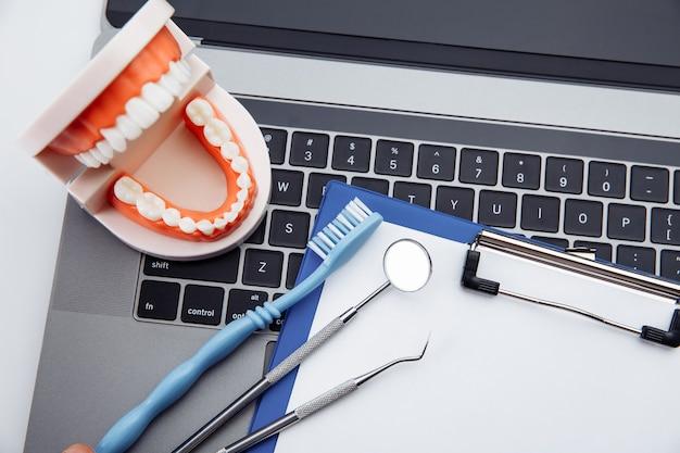 Modello di dente sano con strumento dentista sulla scrivania