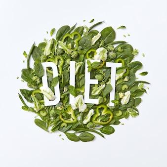 Varietà sana di verdure verdi cavolo, spinaci, asparagi pezzi di cetriolo e pepe su uno sfondo grigio con una scritta di carta dieta su uno sfondo grigio con spazio di copia. lay piatto