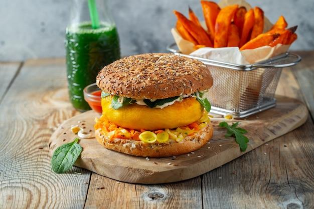 Hamburger vegano sano con verdure fresche e salsa bianca.