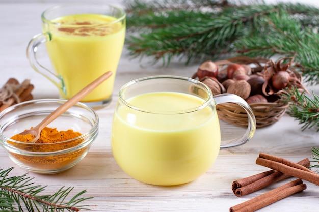 Latte dorato vegano sano, radice di curcuma, zenzero in polvere, cannella su sfondo bianco. spezie per il trattamento ayurvedico. concetto di medicina alternativa.