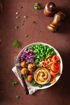 Ciotola di pranzo vegana sana con falafel hummus carota nastri cavolo e piselli