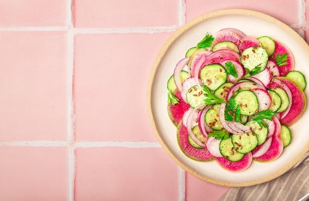 Insalata vegana sana con cetriolo ravanello anguria e cipolla rossa su sfondo di piastrelle rosa vista dall'alto