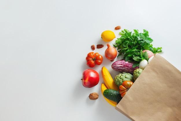 Cibo vegetariano vegano sano in frutta e verdura di sacchetto di carta su bianco