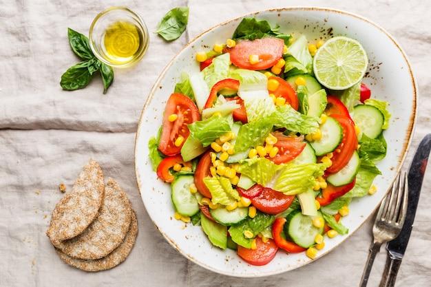 Insalata di verdure sana di pomodoro fresco, cetriolo, lattuga e mais sul piatto, vista dall'alto. menù dietetico.