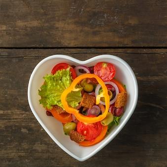 Insalata di verdure sana in un'insalatiera su un tavolo di legno.