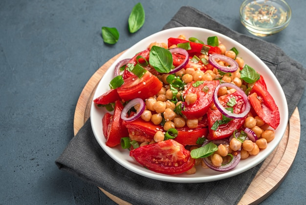 Insalata di verdure sana con ceci, pomodori ed erbe fresche su uno sfondo scuro. vista laterale, primo piano.