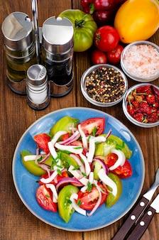 Insalata di verdure sana con pomodori e pezzi di calamaro. foto dello studio.