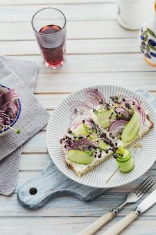 Bruschette vegetariane sane con pane, micro verdure, formaggio, cetrioli e cipolla rossa