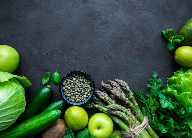 Priorità bassa di concetto di cibo vegetariano sano, selezione di cibo verde fresco per dieta detox su uno sfondo di cemento nero