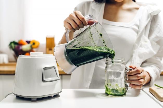 La donna in buona salute gode di produrre il succo verde con le verdure e la frutta verde con il miscelatore