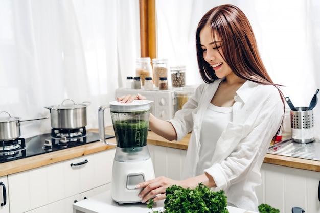 La donna in buona salute gode di di fare la pulizia verde della disintossicazione delle verdure e il frullato verde della frutta con il miscelatore in cucina a casa concetto di dieta. uno stile di vita sano