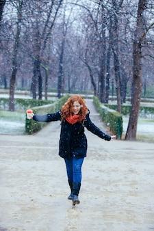 Donna in buona salute che salta su una pozza in un giorno nevoso