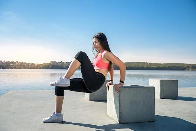Donna in buona salute che riposa e fa esercizio di stretching all'aperto vicino al lago.