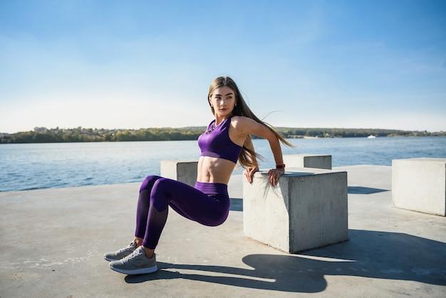 Donna in buona salute che riposa e che fa stretching esercizio all'aperto vicino al lago