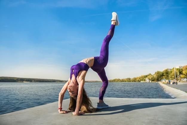 Donna in buona salute che riposa e che fa stretching esercizio all'aperto vicino al lago. Foto Premium