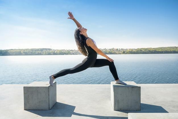 Donna in buona salute che riposa e che fa stretching esercizio all'aperto vicino al lago.