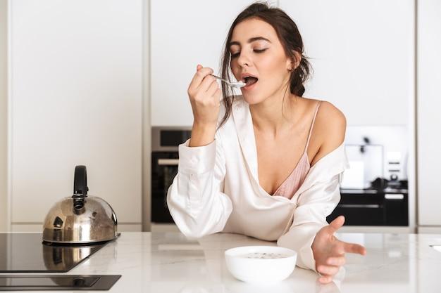 Donna in buona salute che indossa abiti di seta mangiare muesli con latte, mentre si fa colazione in appartamento