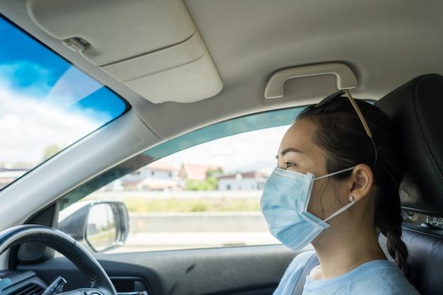 Donna in buona salute con maschera protettiva che guida l'auto