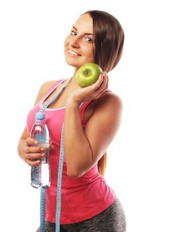Donna in buona salute con acqua e mela dieta sorridente isolato su bianco