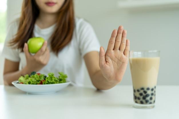 Le donne sane non mangiano tè al latte perlato e scelgono mele e insalata. le donne rifiutano cibi e bevande ma mangiano cibi vitaminici sani. concetto di dieta e buona salute.