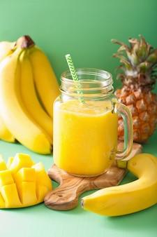 Frullato giallo sano con banana ananas mango in barattoli di vetro