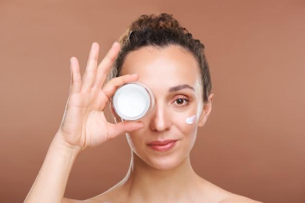 Giovane bella donna in buona salute che tiene piccolo vasetto di crema per il viso ringiovanente ad occhio mentre in piedi davanti alla telecamera in isolamento