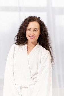 Sana giovane donna affascinante con un sorriso a trentadue denti che indossa un morbido accappatoio bianco dopo il bagno mattutino
