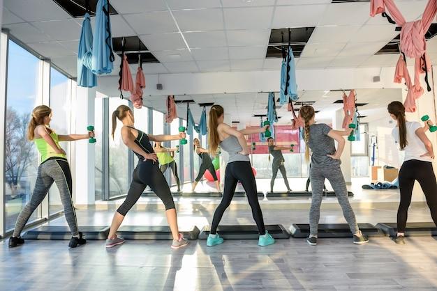 Sano, giovane gruppo di donne che fanno esercizi in palestra