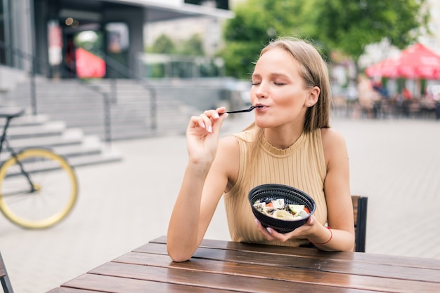 Giovane donna in buona salute che mangia insalata all'aperto in street cafe