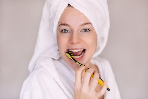 Giovane donna in buona salute con spazzolino da denti che pulisce i suoi denti in bagno
