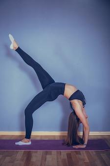 Donna sana che fa yoga o sport in appartamento industriale o palestra