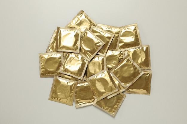Mucchio di preservativi in bianco sul muro grigio chiaro